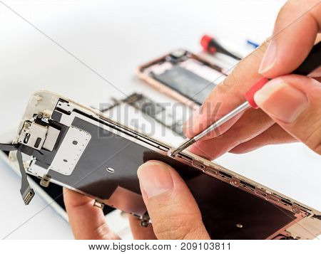 Close-up of technician being unlock screw with screwdriver on blurred smartphone component background