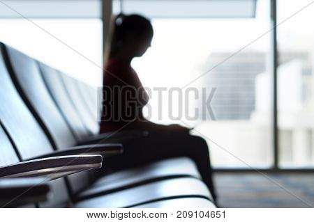 Silhouette woman in airport waiting room. Person sitting on bench before flight in terminal and departure lounge. Travel, holiday and transportation concept.