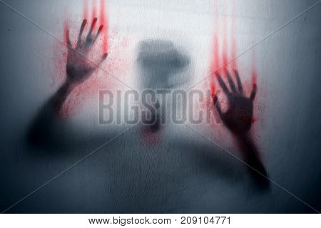 Angry ghost with bloody hands covered by sheet