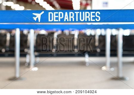Departures text with airplane icon on a queue barrier. Waiting area and lounge seats at airport terminal. Travel, vacation and tourism concept.