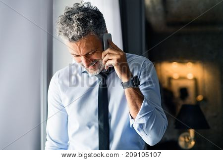 Mature businessman with smartphone in a hotel room. Handsome man standing at the window, making a phone call. Close up.