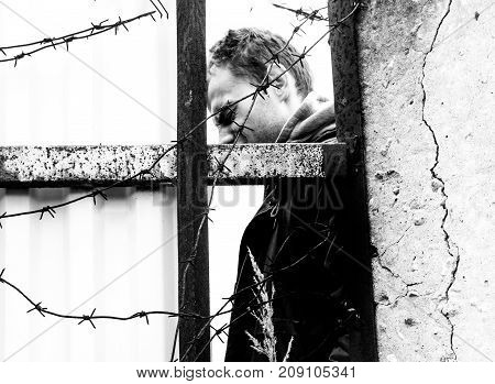 man behind barbed wire with sad face prisoner in prison concept