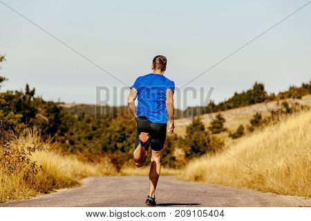 back male runner dynamic running on road autumn yellow grass of field