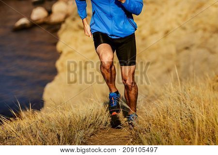 muscular legs of runner man running on trial mountain sea bay