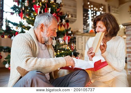 Senior couple sitting on the floor in front of illuminated Christmas tree inside their house giving presents to each other, woman unwrapping her gift.