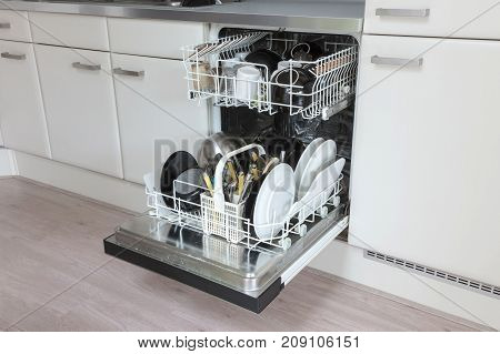 Open Dishwasher With Clean Plates, Cups And Dishes
