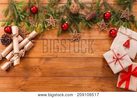 Christmas decoration, gift boxes in craft paper with twine rope and garland frame background, top view on wood table surface. Christmas ornaments and presents border with balls and stars, copy space