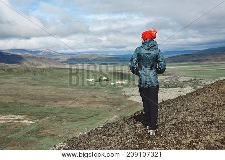 Girl in warm clothing observing surroundings on background of mountains of Iceland.