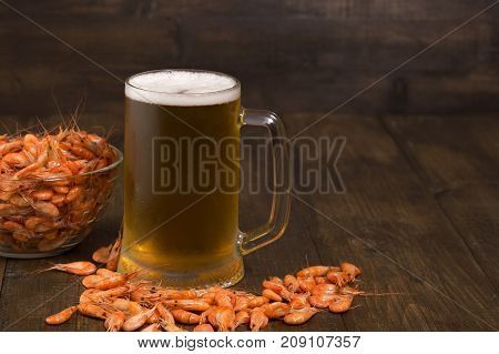 Glass mug of light beer and fresh boiled shrimp in a glass bowl on a dark wooden table
