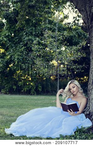 woman in blue dress reading a book leaning on tree