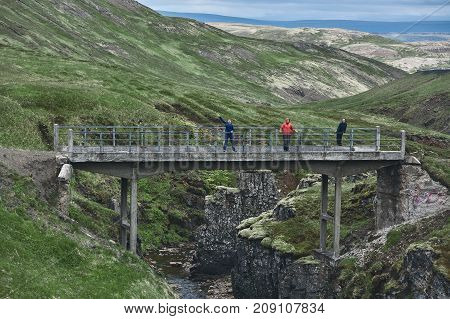 people hikers on the old stone bridge over the gorge with a stream in the mountains in Iceland