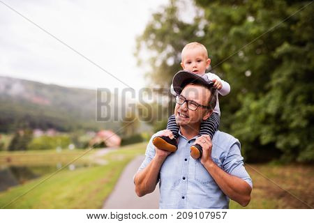 Father and little boy spending time together outside in green nature. Young man carrying toddler son on his shoulders.
