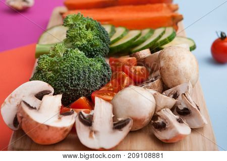 Healthy food background. Cut raw vegetables on wooden board. Chopped and sliced ingredients for salad or soup - mushroom, cherry tomato, broccoli, cucumber, carrot on bright background