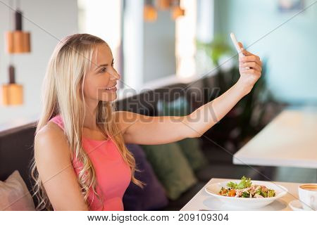 technology and leisure concept - happy woman with smartphone taking selfie at restaurant