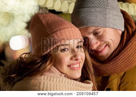 love, romance and people concept - close up of happy couple in winter clothes