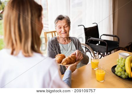 Health visitor and a senior woman during home visit. A nurse giving food to an elderly woman sitting at the table.