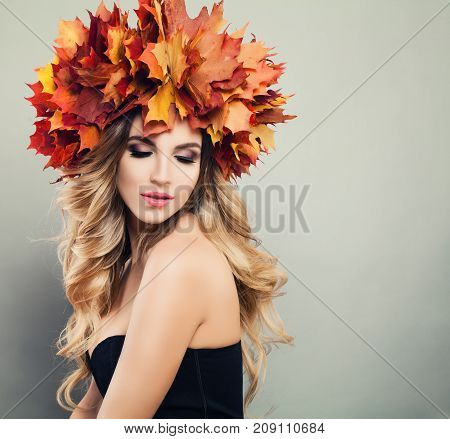 Autumn Beauty. Beautiful Woman Spa Model with Wavy Blonde Hair Makeup and Fall Leaves Wreath on Gray Background with Copy space