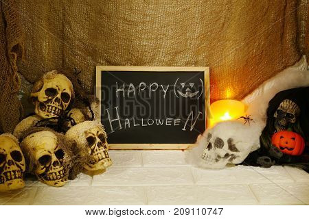 Halloween decoration pumpkin candles and horror skull on wall background