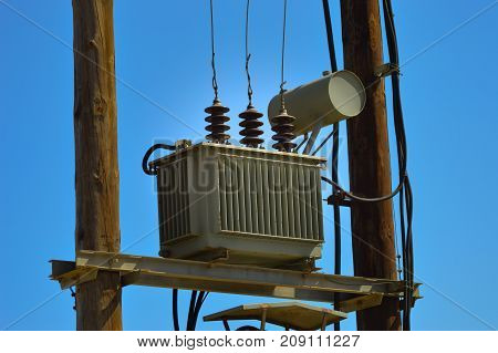 Electric transformer on wooden pylons with an arrival and several departures and countless recreations
