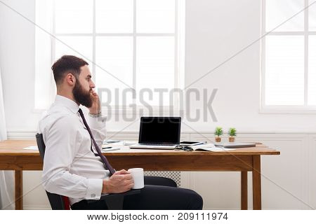 Businessman in formal clothes has conversation by mobile phone with laptop in modern white office