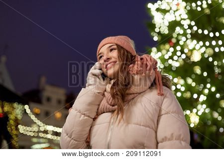 holidays, communication and people concept - portrait of beautiful happy young woman calling on smartphone at christmas tree in winter evening