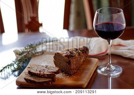 bread and a glass of wine on a wooden board and table