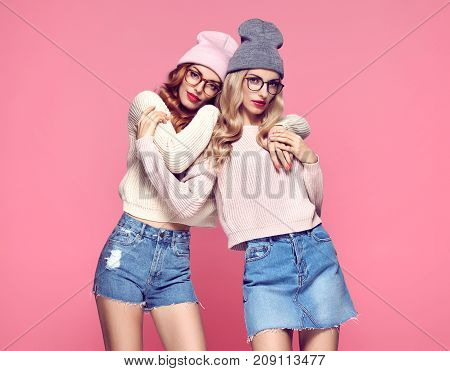 Fashion. Young woman Hugging in Stylish Autumn outfit. Pretty Sisters Best Friends Twins. Hipster Blond Redhead Model, fashion Cozy jumper, Glasses. Beautiful Girls in Trendy Beanie hat on Pink