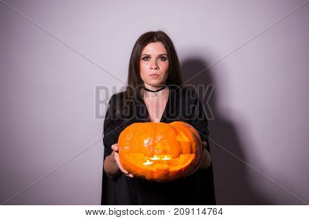 Jack o Lantern Halloween pumpkin grinning in the most evil fashion in woman's hands