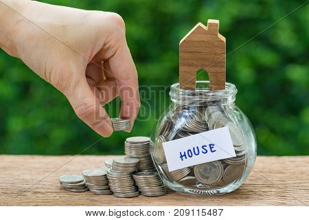 Woman hand holding stack of coins money and glass jar with full of coins and miniature wooden house label as House property or mortgage concept.