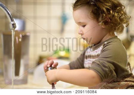 Сute two-year girl washes the dishes in kitchen