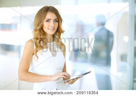 Blonde woman with touchpad computer looking at camera and smiling while business people are shaking hands over office background