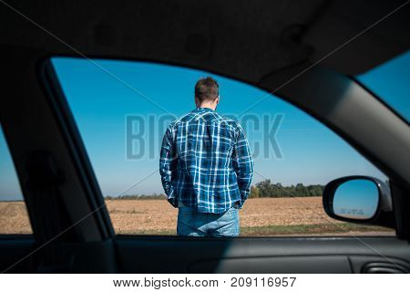 man stands on a road view from the car window