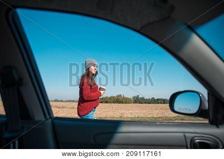 woman in hat opening car door on highway