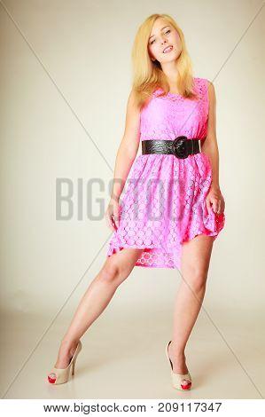 Fashion clothing concept. Lovely young woman wearing short pink feminine dress with big black belt. Studio shot on white background