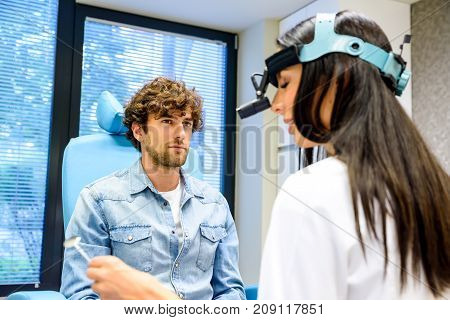 A female ENT specialist during a examination