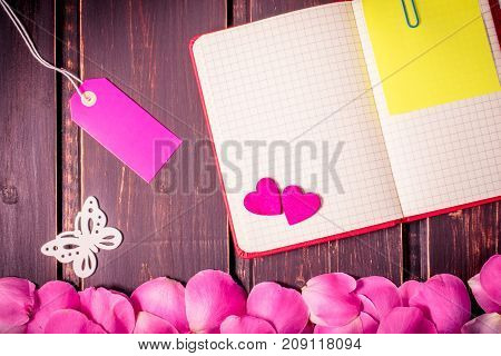 blank note book close-up with rose leaves, hearts, sale label, butterfly and copy space on wooden background. Spring border template and floral mockup. sale, greeting and celebration card concept.