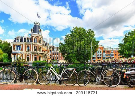 Traditional dutch bicycles parked along the street at Museumbrug bridges over canal of the most romantic city Amsterdam in summer. Cityscape with old buildings, trees and flowers, Netherlands, Europe.