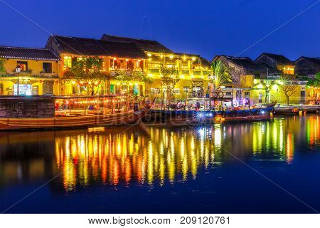 HOI AN VIETNAM - 4/19/2016: Lights from Hoi An Vietnam riverside cafes and shops reflect off the water.