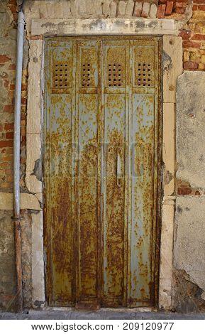 An old rusty metal door in a disused building on the Venetian island of Giudecca