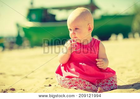 Small child sitting playing and having fun on the beach near the sea.