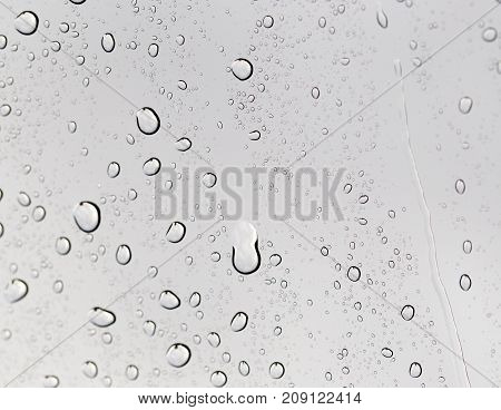 Drops of rain on the inclined window glass . Photo of abstract background