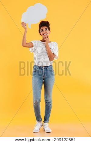 Full length image of smiling pensive african woman looking up and holing blank speech cloud over yellow background
