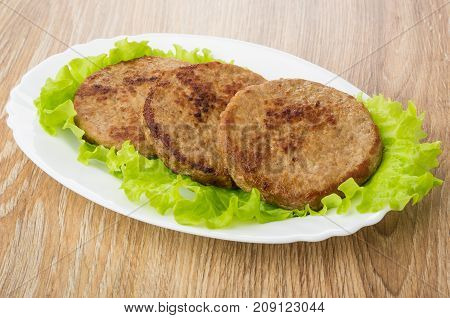 Fried Cutlets With Leaves Of Lettuce In Oval Dish