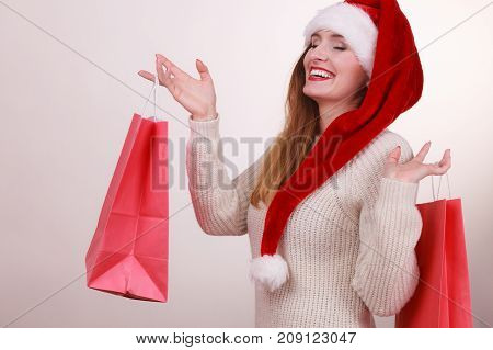 Christmas time. Young latin woman wearing santa claus hat holding red shopping bags buying presents gifts