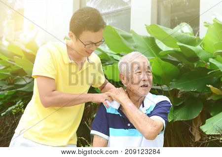 Asian old man shoulder pain son massaging father shoulder. Chinese family senior retiree outdoors living lifestyle in the garden.
