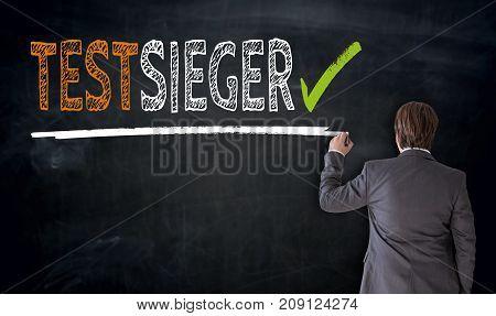 Businessman Writes Testsieger (in German Test Winner) On Blackboard Concept