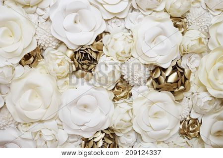 Wall with beautiful artificial white and gilt flowers, close up