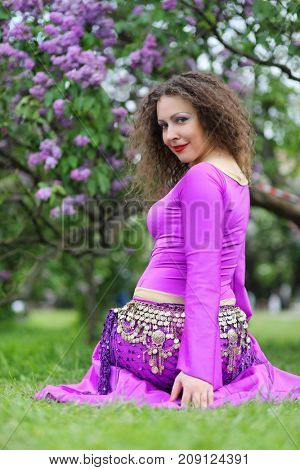 Woman in purple costume for belly dance poses on lawn near bushes of blossoming lilacs at spring