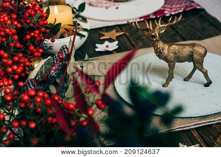 Toy Golden Reindeer, On The Plate At The Christmas Table, Surrounded By Nandinas