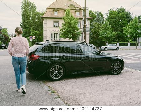 STRASBOURG FRANCE - JUN 25 2017: Casual French woman walking past a black luxury BMW wagon care in an upper-class neighbourhood in Strasbourg France